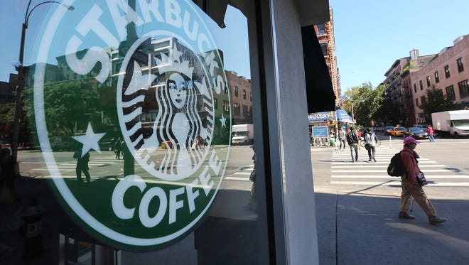 """A woman walks past a Starbucks cafe in Manhattan on Sept. 18, 2013 in New York City. A parody of the coffee shop called """"Dumb Starbucks"""" opened in Los Angeles Feb. 7."""
