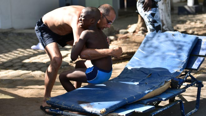 A man helps a wounded child after heavily armed gunmen opened fire on March 13, 2016, at a hotel in the Ivory Coast beach resort of Grand-Bassam.