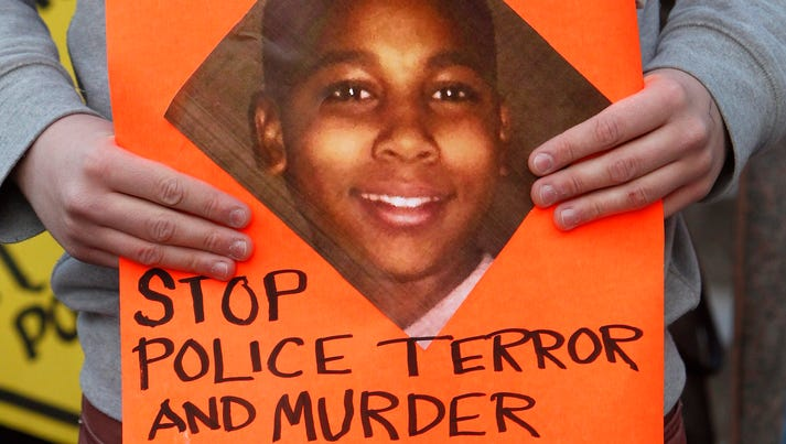 A Cleveland protester holds a sign with a picture of