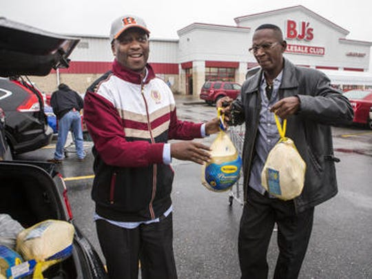 Norman Oliver (left) and his friend Tyrone Brown load turkeys into Brown's car at B.J.'s Wholesale Club near New Castle on Tuesday afternoon. Oliver has operated a Thanksgiving Turkey Giveaway since he was a freshman in college.