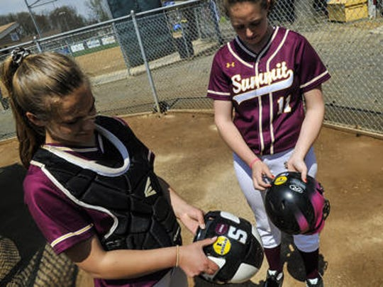 Summit's Veronica Thompson, left and Kendall Blomfield place commemorative decals on their batting helmets in honor of 9-year-old Leah Hansen. Leah recently suffered what is believed to be a spinal cord stroke.
