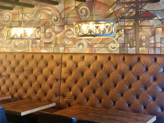 A mural of Milwaukee scenes is painted over banquette seating at the new View MKE on Hubbard St.