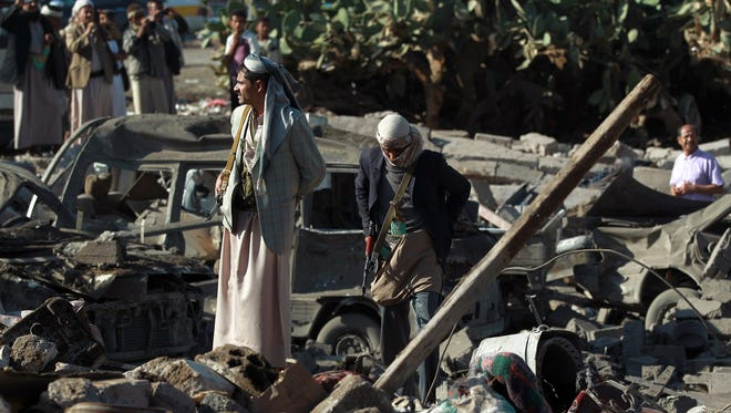 Yemeni Houthi fighters stand at the site of a Saudi airstrike against rebels near Sanaa Airport on March 26, 2015.