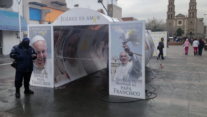 A police officer patrols on Jan. 5, 2016 in Juarez, Mexico, in front of a Pope Francis installation advertising the pope's upcoming visit the city. Juarez, on Mexico's northern border across from El Paso, Texas.