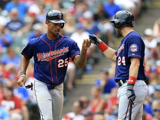 Minnesota Twins rookie center fielder Byron Buxton (25) celebrates with third baseman Trevor Plouffe (24) after scoring the winning run in a victory over the Texas Rangers during his major-league debut Sunday afternoon.