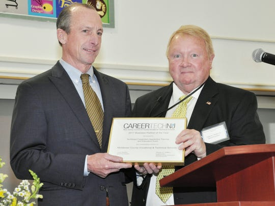 MCVTS Board of Education President Eugene Mullen, right, presents the district's annual Business Partner of the Year Award to Ridgeley Hutchinson, executive director of the New Jersey Carpenters Apprentice and Training Fund.