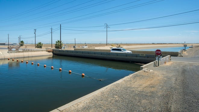 This July 23, 2015 photo provided by the California Department of Water Resources shows The Russell Avenue bridge, over the Delta Mendota Canal in Firebaugh, Calif., The  drought has caused the bridge to subside until there's almost no space between bottom of bridge decking and canal water surface. A NASA scientist says in a report released Wednesday, Aug. 19, 2015 that parts of California's Central Valley are sinking faster than ever as groundwater is being pumped during the state's historic drought. (Florence Low/ California Department of Water Resources via AP)