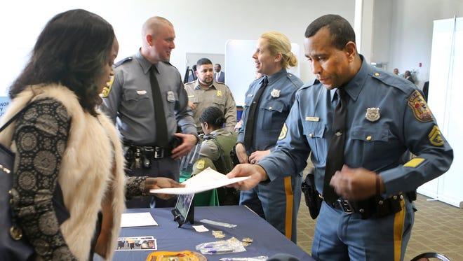 Tamara Simeon, a senior at Delaware State University from Orange, New Jersey, hands her completed application to Stanley Jiminez, of the Delaware State Police, at the National Organization of Black Law Enforcement Executives (NOBLE) 10th annual law enforcement career fair, held Tuesday on the DSU campus.