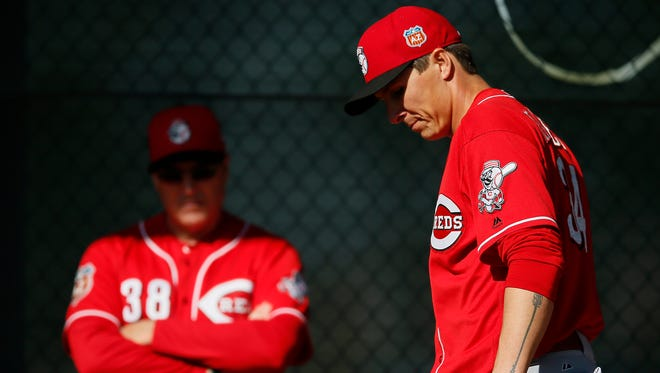 Reds pitcher Homer Bailey (right) gets set on the mound as manager Bryan Price looks on during a brief bullpen session at spring training.