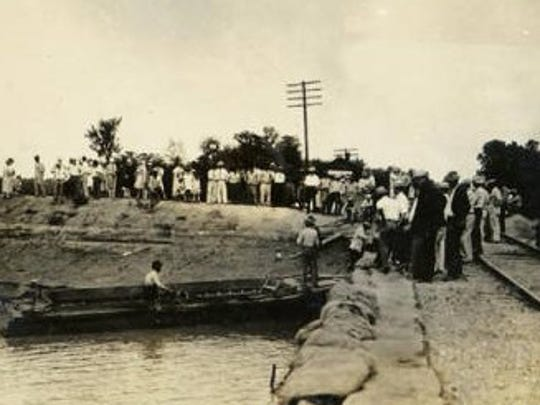 People stand along a levee at Simmsport, Louisiana, during the 1927 flood.