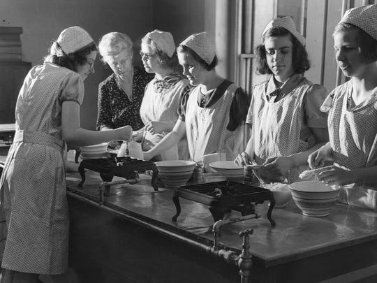 Students learn cooking techniques. 1940