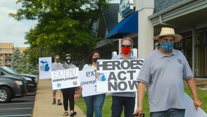 Demonstrators gather outside of U.S. Rep. Bill Huizenga's office in Grandville, Mich. on Thursday, July 23, to call for an extension of the federal government's unemployment benefits. While the benefits will officially expire at the end of July, Congress remains split on how to address the next unemployment relief package.