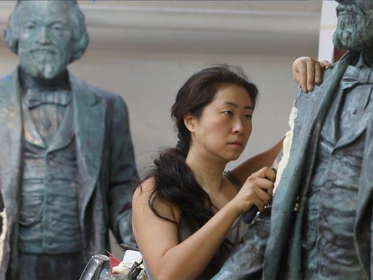Olivia Kim, a sculptor, works on finishing three Frederick