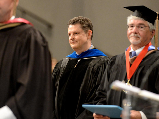 Dr. Jan Wilms awaits the his two son's names to be called during University School of Jackson's 2015 commencement ceremony.