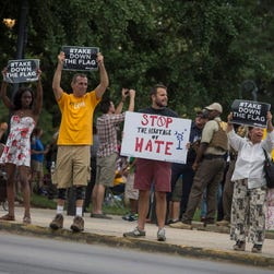 People hold up signs saying #TakeDownTheFlag at a rally calling for the Confederate battle flag to be taken down at the South Carolina Capitol in Columbia on June 20, 2015.