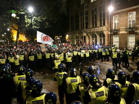 Police try and block masked demonstrators as they march