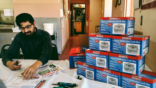 Youth Substance Abuse Coalition coordinator, A.J. Sandoval sits at the HMS Silver City Senior Center with the complimentary lock boxes distributed to seniors who took a pledge to secure their medications.