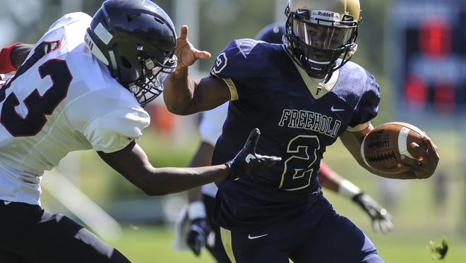 Freehold Boro quarterback Ashante Worthy stiff-arms  Neptune's Hassan Worthy on his way down the field in the first quarter during their game in Freehold on  Sept. 23, 2017.