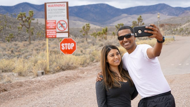 Reece D'Silva (holding camera) and Alexis Esparza take a selfie outside the entrance to Area 51 in Nevada while on a tour of the Extraterrestrial Highway.
