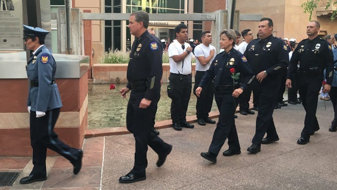 Phoenix officers walked in a procession to the memorial wall, holding roses to honor the lives of fallen officers.