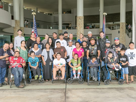 Members of the Legends Motorcycle Club pose for a photograph with the recipients of wheelchairs they donated.