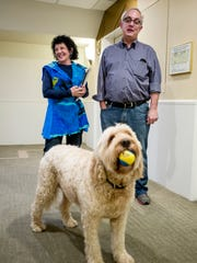 Mitch and Freada Kapor wait for the elevator with their dog 'Dudley' at the downtown Oakland offices of The Kapor Center for Social Impact.