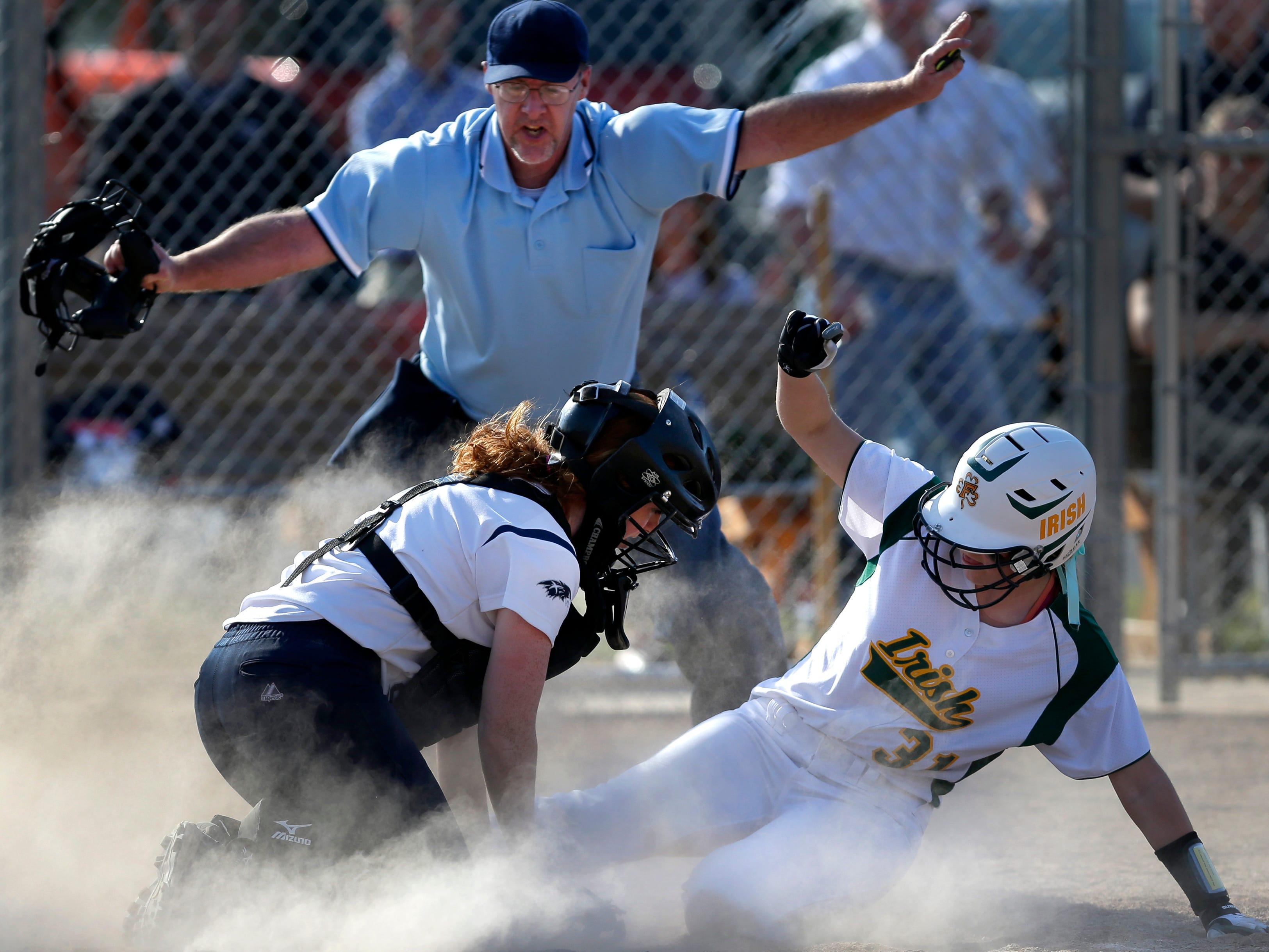 Freedom's Lori Meyer slides under the glove of Xavier catcher Maria Hollenbach during Friday's game at Xavier.