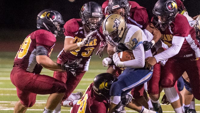 Tulare Union defenders swarm Monache's Aidan Galvan in an East Yosemite League football game on Thursday, October 5, 2017.