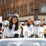 Minnesota Lynx basketball players Seimone Augustus, left, and Maya Moore, right, react to fan cheers during an Oct. 16 parade to celebrate the team's WNBA championship win.