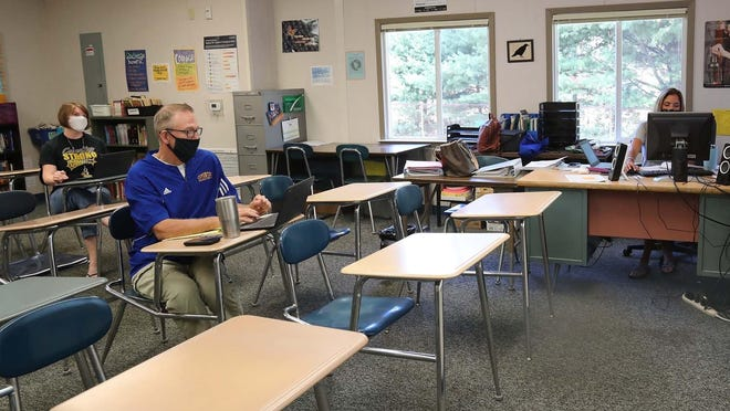 Coventry Middle School teachers Jen Bruns, left, John Murray and Carrie Jacobs during online training Friday for setting up their classes.