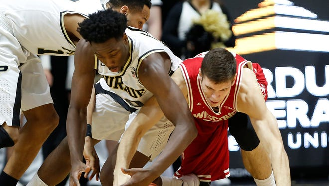 Caleb Swanigan wrestles Ethan Happ of Wisconsin for a loose ball Sunday, March 6, 2016, at Mackey Arena. Purdue defeated Wisconsin 91-80.