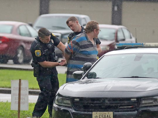 Green Bay Police Officers adjust the handcuffs on a man during investigation of a stabbing in the 2700 block of Humboldt Road  in Green Bay.