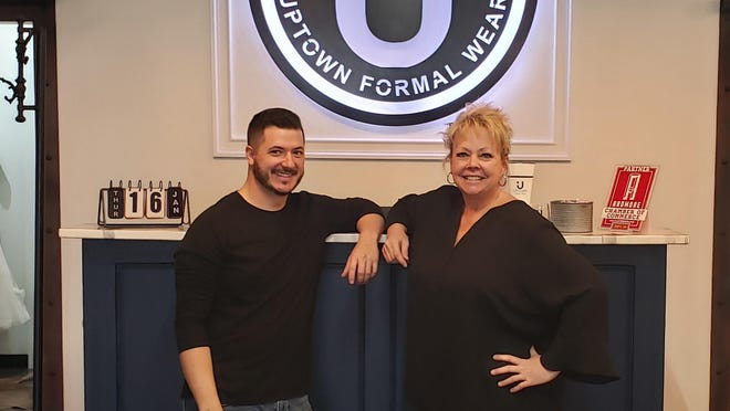 Joseph and Lori Clinton in front of the register of their new business, Uptown Formal Wear. The store has a wide selection of gowns for brides, bridesmaids and prom as well as offering tuxedo rentals.