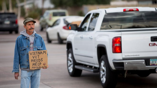Stephen Quick, 60, panhandles on the corner of Apache and Price, in Tempe, on Oct. 18, 2014. Quick was trying to raise $45 for a night in a hotel room. He says he doesn't like the shelter.