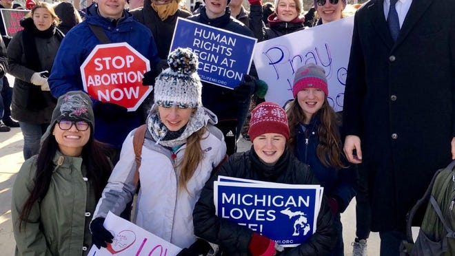 The same high school Right to Life group from Hillsdale Academy that distributed roses recently at Hillsdale Market House went to the Capitol Jan. 27 for a rally. Rep. Andrew Fink, right, stopped to encourage the students.