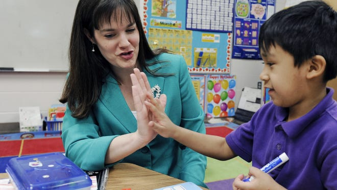 In this file photo, Tennessee Education Commissioner Candice McQueen, left,  gives a high-five to Whitsitt Elementary kindergartener Bryan Gamboa during class on Monday March  9, 2015.