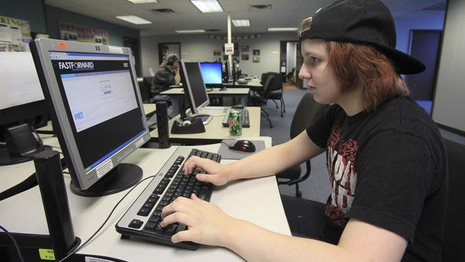 Sarah Norris, 17, works on social studies courses on a computer at the Youth Career Center as she tries for her GED.