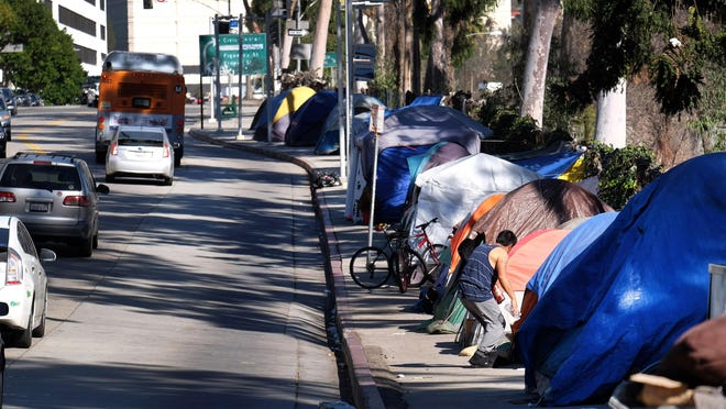 FILE - This Tuesday, Jan. 26, 2016 file photo shows tents from a homeless encampment line a street in downtown Los Angeles.With California's homeless situation at a crisis level, state officials are negotiating a plan to provide up to $2 billion to help cities build permanent shelters that would get mentally ill people off the street. (AP Photo/Richard Vogel,File)