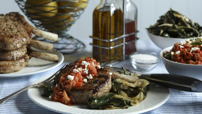 Pork chops are served with a roasted red pepper and feta cheese relish, plus a side of sauteed greens.