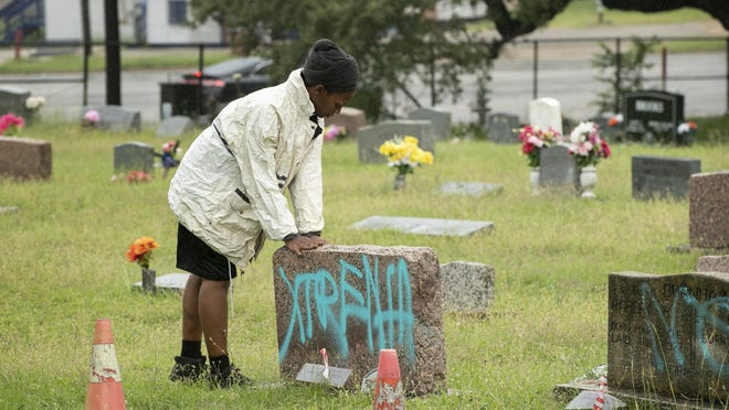 A woman blesses the defaced headstones at Evergreen Cemetery on Monday.