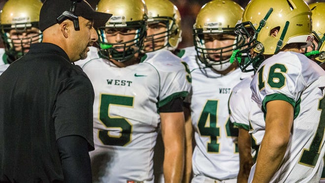 Iowa City West High Head Coach Brian Sauser talks to his quarterback Nate Boland (16) and the rest of the offensive unit during a timeout versus Iowa City High at Bates Field in Iowa City on Friday October 11, 2013 for the Annual Battle for the Boot. (Justin Torner/Freelance for the Press-Citizen)