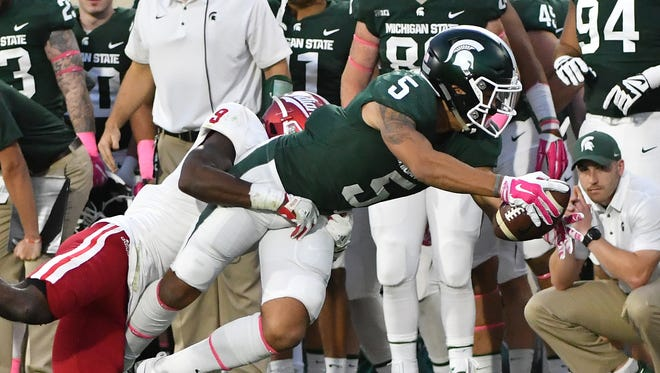 Michigan State's Hunter Rison stretches out for a first down with Indiana's Jonathan Crawford defending in the fourth quarter.