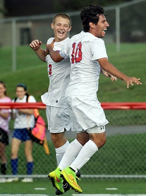 Fairport's Anthony Gaglianese, right, celebrates the first of his two goals with teammate Christopher Barker during a game played at Fairport High School on Sept. 4, 2014.