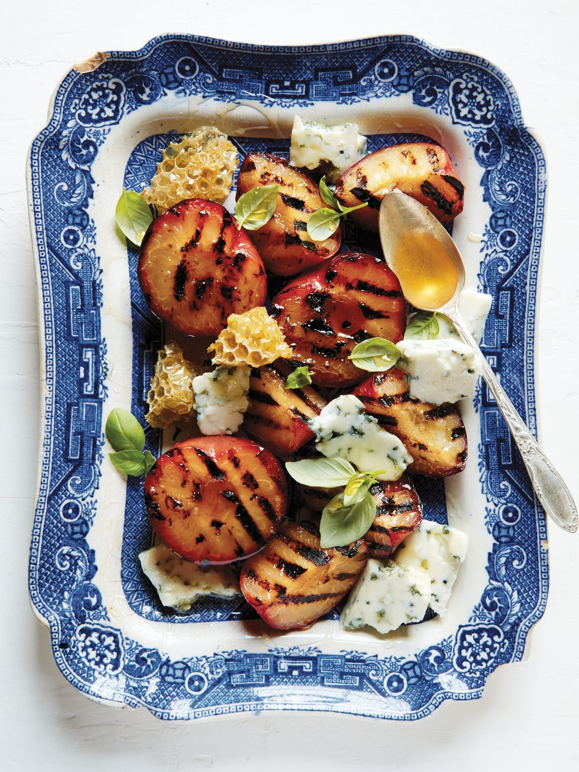 Grilled Stone Fruit, Blue Cheese & Honey Serves 4  When you can't decide between a dessert and a cheese course, make this dish. It's a little savory, a little sweet, and perfectly balanced — and just the thing when the grill's been fired up all day but you're not quite ready to let those nice, hot coals go. If blue cheese is not your flavor, fresh ricotta would be equally lovely here.  Ingredients 4 stone fruits such as apricots, peaches or plums, halved and pitted Olive oil 1 teaspoon Maldon salt 1 small wedge (about ¼ pound) best-quality blue cheese 1/4 cup best-quality honey Small basil leaves  Directions Prepare the grill (see text below for tips). Brush the fruit halves with olive oil and sprinkle with salt. Put them flesh-side down on a hot grill and cook just until you get some good grill marks on the fruit, about 4 minutes. Turn the fruit and grill for another 2 minutes. Transfer the fruit to a platter, garnish with a bit of blue cheese, a drizzle of honey, and a sprinkling of basil and serve.