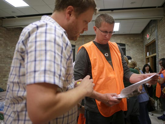Chris Lashock, client services coordinator with Homeless Connections, goes over last-minute details with John Weyenberg, executive director of the Greater Fox Cities Area Habitat for Humanity, before heading out on their routes for a point-in-time homeless count late Wednesday.