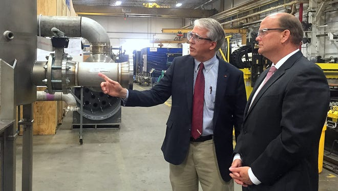 """U.S. Rep. Tom Reed, right, listens as Hilliard Corp. Chairman Arie """"Jan"""" van den Blink explains some of his company's manufacturing processes during a facility tour Monday."""