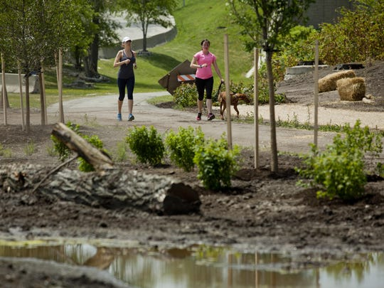 Two people run past a pond where restoration work is underway Wednesday, June 17, 2015 at the County Wetlands Park on the Blue Water River Walk in Port Huron.