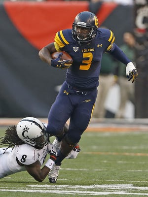University of Toledo's Kareem Hunt, 3, is tackled by University of Cincinnati's Adrian Witty, 8, during the first quarter of their 2014 game 2014 in Cincinnati.