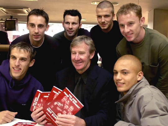"In this March 1, 2001 file photo, Eric Harrison, center, poses for a photo with Manchester United players from left, Gary Neville, Phil Neville, Ryan Giggs, David Beckham, Nicky Butt and Wes Brown during his book launch, at Old Trafford, in Manchester, England. Harrison, the Manchester United youth team manager who launched the career of David Beckham as part of the renowned group of ""Class of 92"" players, has died."
