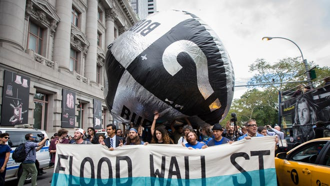 Demonstrators march towards Wall Street from Battery Park to protest for action on climate change and corporate greed, Monday, Sept. 22, 2014, a day after a huge climate march in New York City. (AP Photo/John Minchillo)